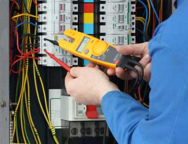 electrician testing voltage at fuse box